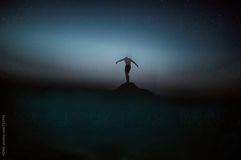 A man stands on top of a mountain at dusk by HOWL for Stocksy United