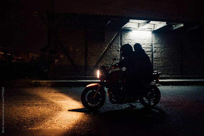 Two men riding a motorcycle by Boris Jovanovic for Stocksy United