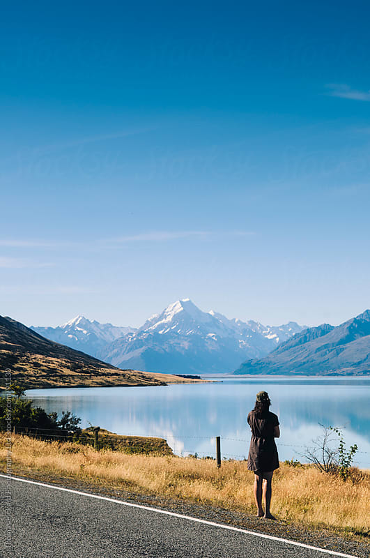 Woman looking towards Aoraki / Mt Cook, the highest mountain in New Zealand. by Thomas Pickard for Stocksy United