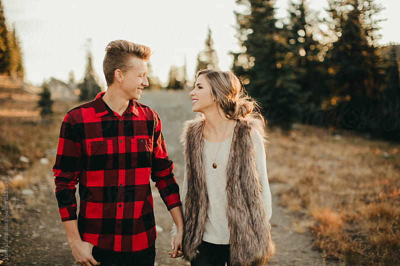 Young engaged  couple laughing on mountain road by Luke Liable for Stocksy United