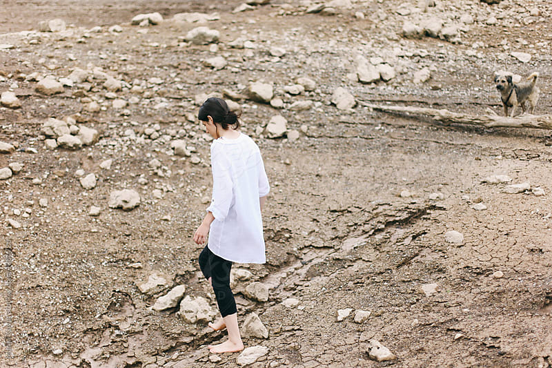 Woman walking on the rocks by Marija Kovac for Stocksy United