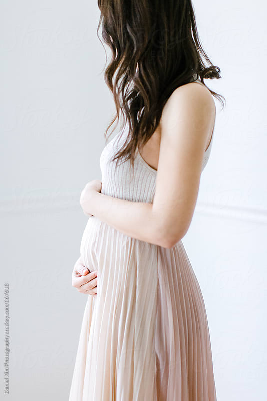 Woman holding pregnant belly by Daniel Kim Photography for Stocksy United