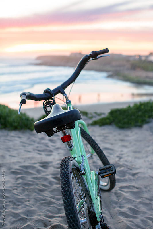 Mint green cruiser bike parked at the beach at sunset by Carolyn Lagattuta for Stocksy United