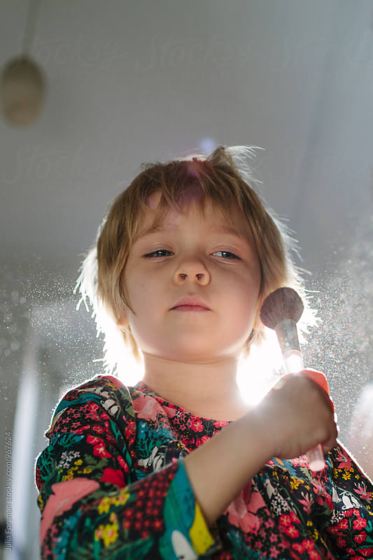 A little girl uses a brush to put on face powder. by Julia Forsman for Stocksy United