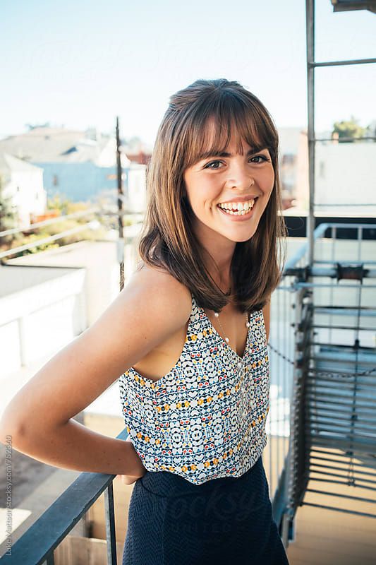 Smiling Attractive Young Woman Smiling On Fire Escape by Luke Mattson for Stocksy United