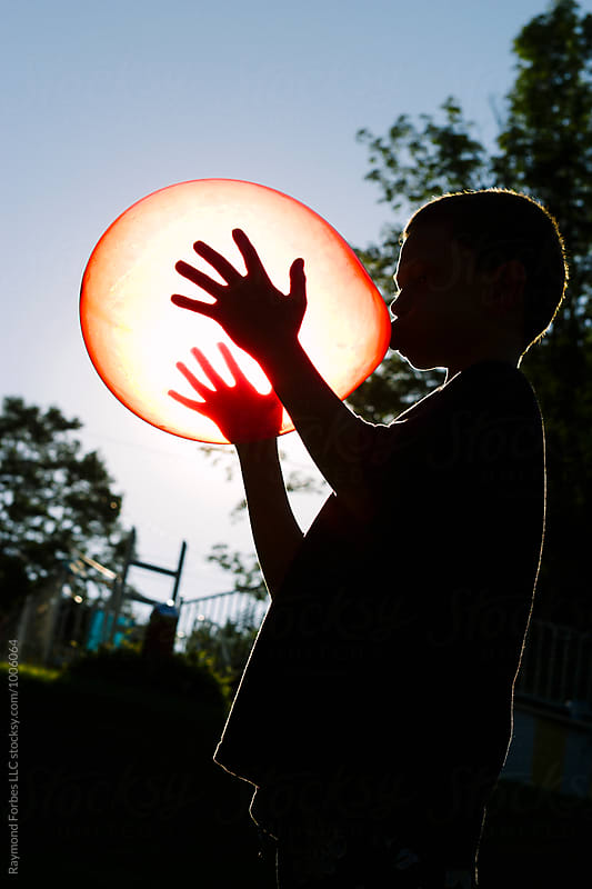 Boy Inflating Balloon on Hot Summer Day by Raymond Forbes LLC for Stocksy United