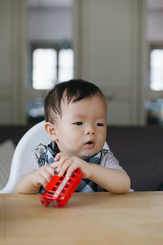 baby boy play toy by jira Saki for Stocksy United