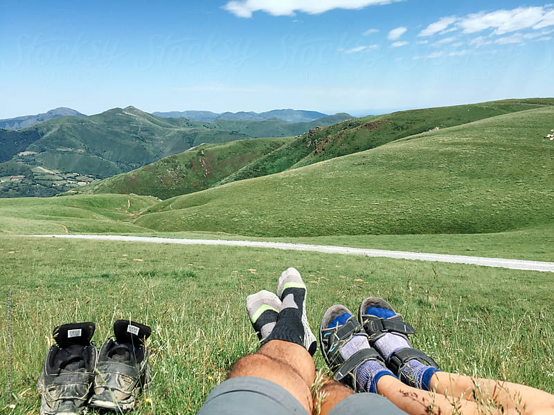 Two hikers barefoot relaxing on the grass  by Luca Pierro for Stocksy United