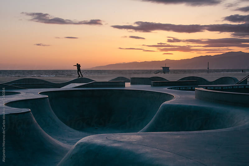Man skating with skateboard on a skatepark at sunset with beach on background in Venice beach by Alejandro Moreno de Carlos for Stocksy United