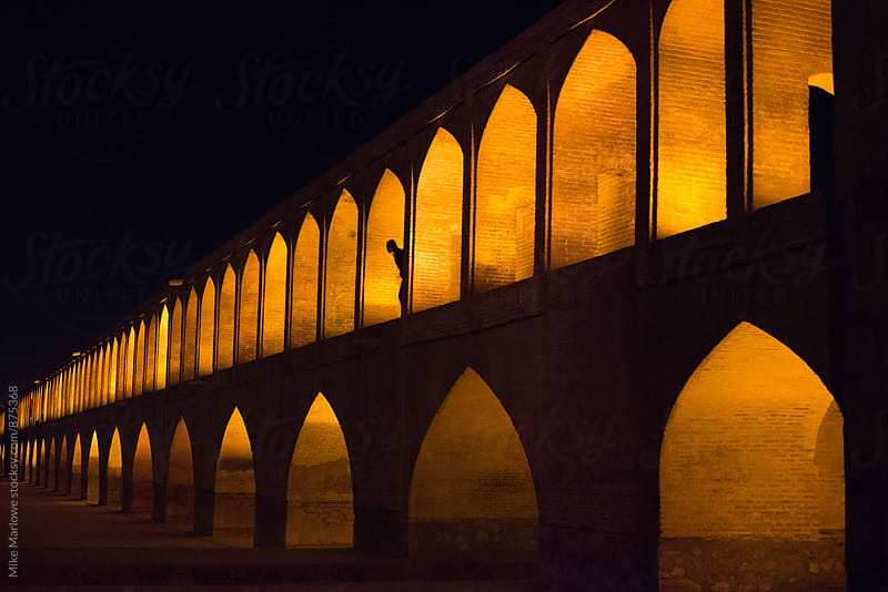 Illuminated brige at night in Esfahan, Iran with person looking out by Mike Marlowe for Stocksy United