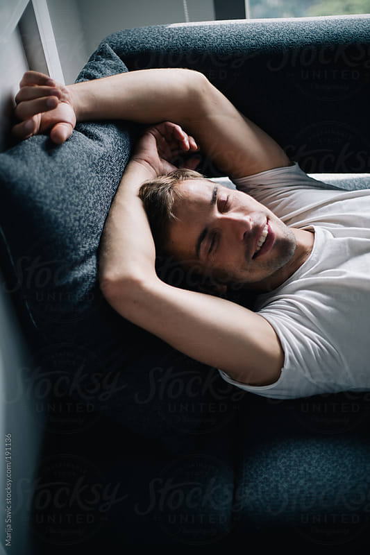 Man Smiling in Bed by Marija Savic for Stocksy United