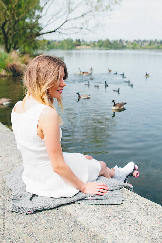 Young woman watches ducks by Jesse Morrow for Stocksy United