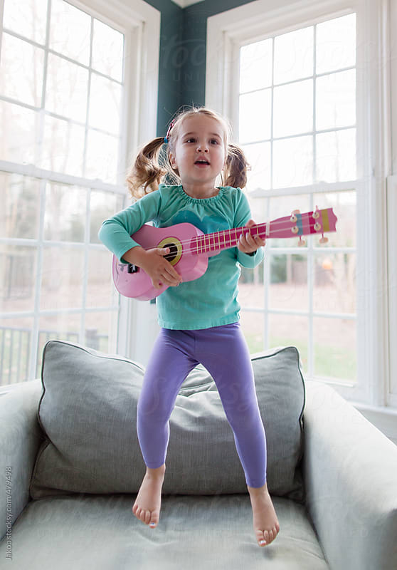 Toddler playing with a toy guitar by Jakob for Stocksy United
