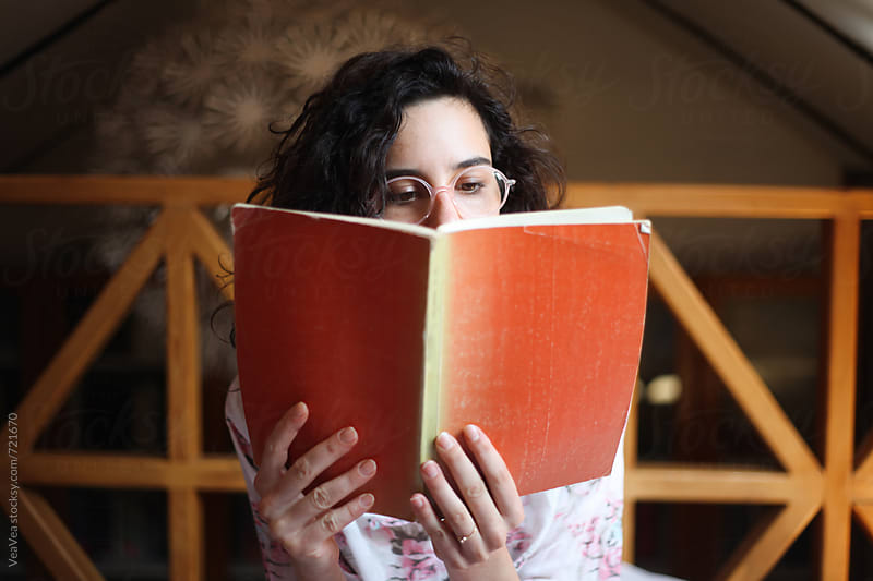 Portrait of a brunette woman with glasses and a book  by Marija Mandic for Stocksy United