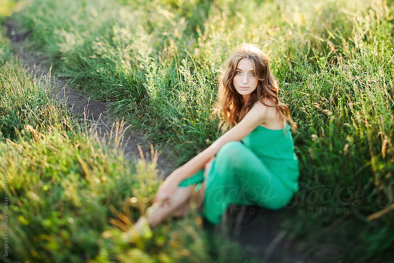 Young brunette female sitting on the grass  by Sergey Filimonov for Stocksy United