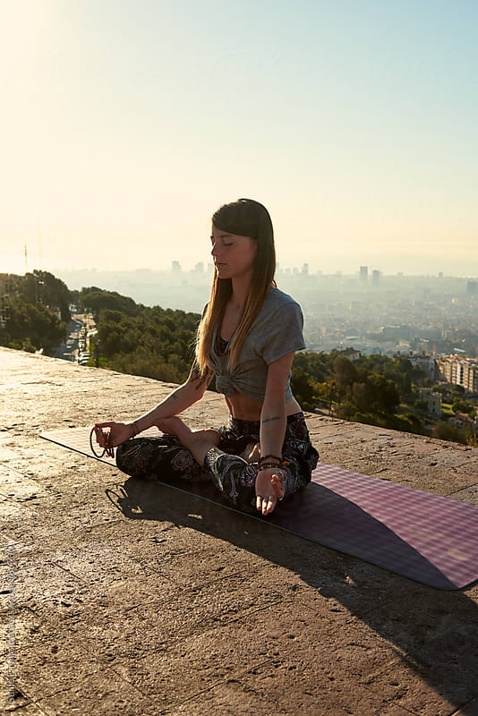 Young woman sitting in lotus position against of Barcelona cityscape by Guille Faingold for Stocksy United