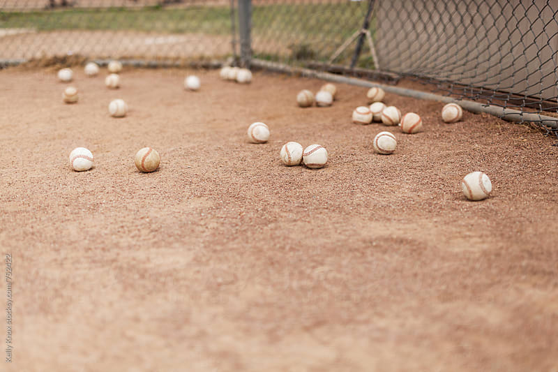 baseballs behind home plate during batting practice  by Kelly Knox for Stocksy United