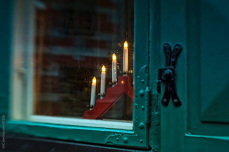 Christmas lights on a window sill in Sweden by Simone Becchetti for Stocksy United