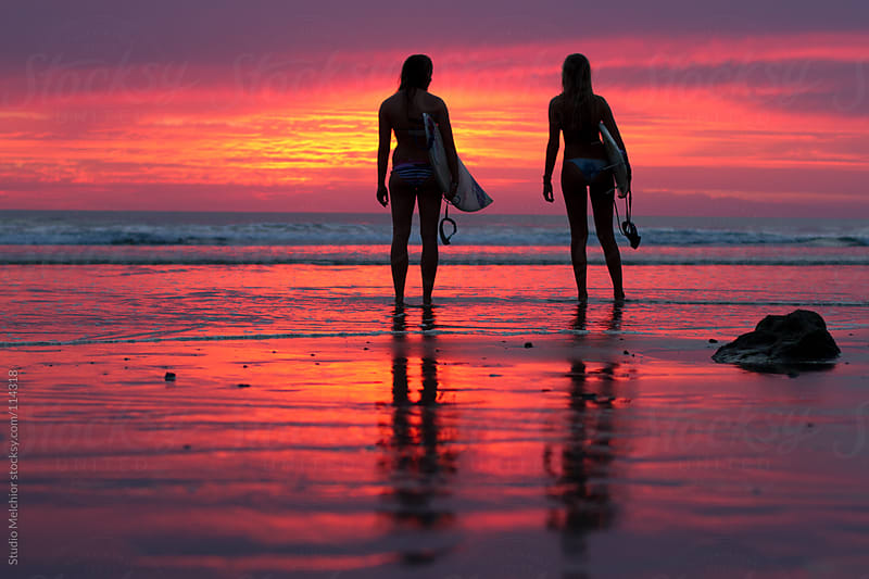 Surfer girls with surfboards looking at the sunset by Melchior van Nigtevecht for Stocksy United