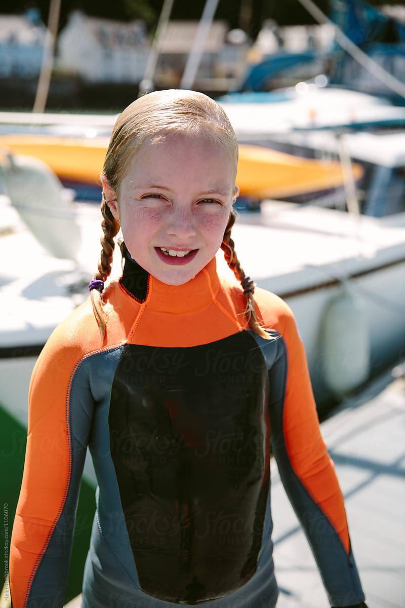 A Little Girl Wet From The Sea In A Wetsuit Smiling  Stocksy United-3955