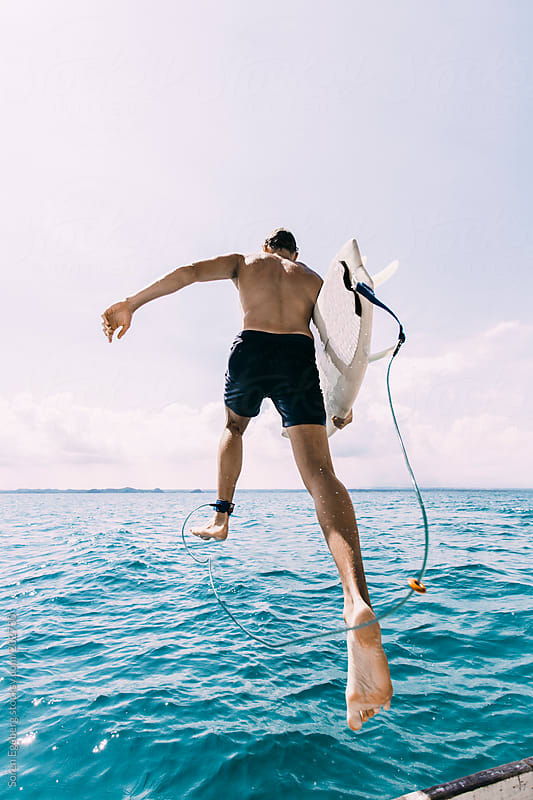 Young surfer jumping in the blue sea from boat with surfboard in summer by Soren Egeberg for Stocksy United