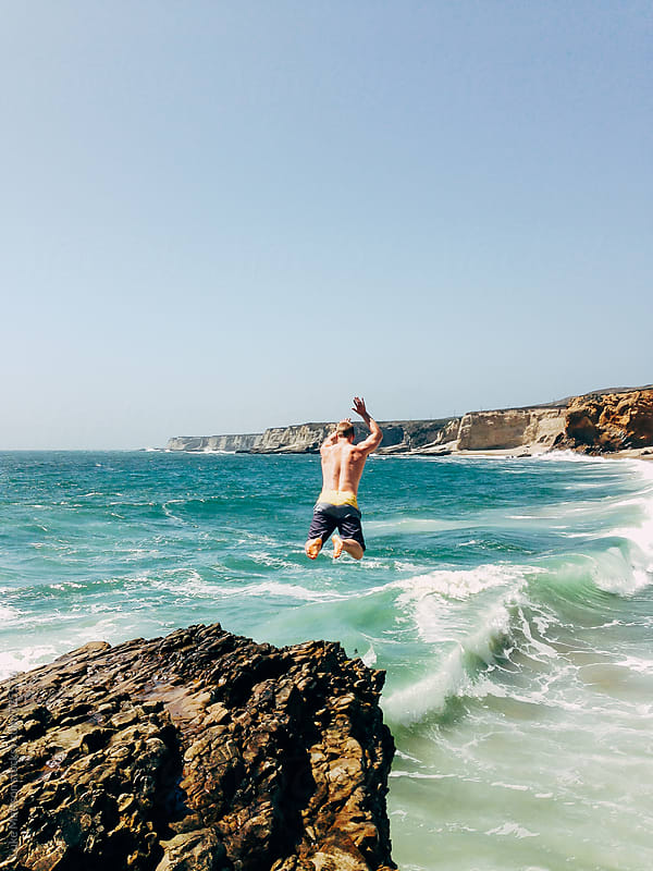 Man Jumping From A Rock Cliff Into The Ocean Waves by Luke Mattson for Stocksy United