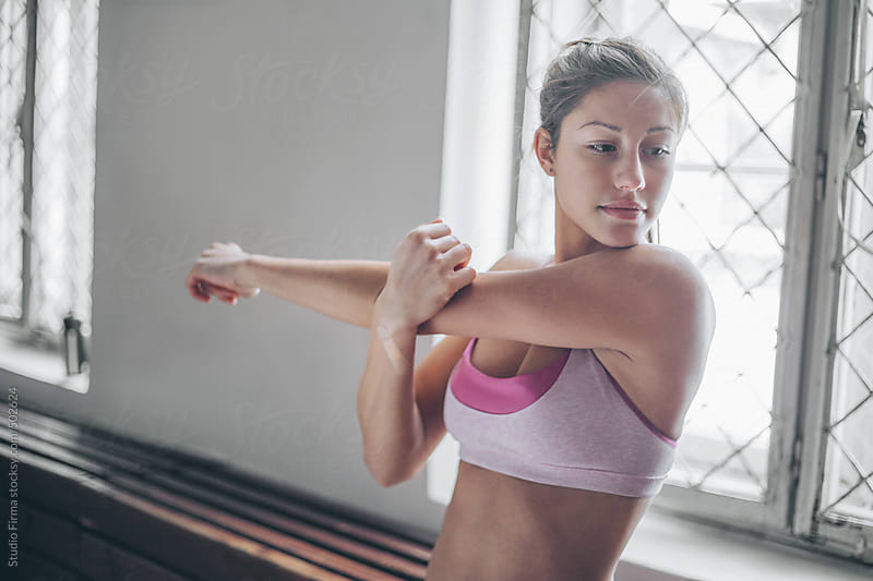 Woman stretching during exercise. by Studio Firma for Stocksy United