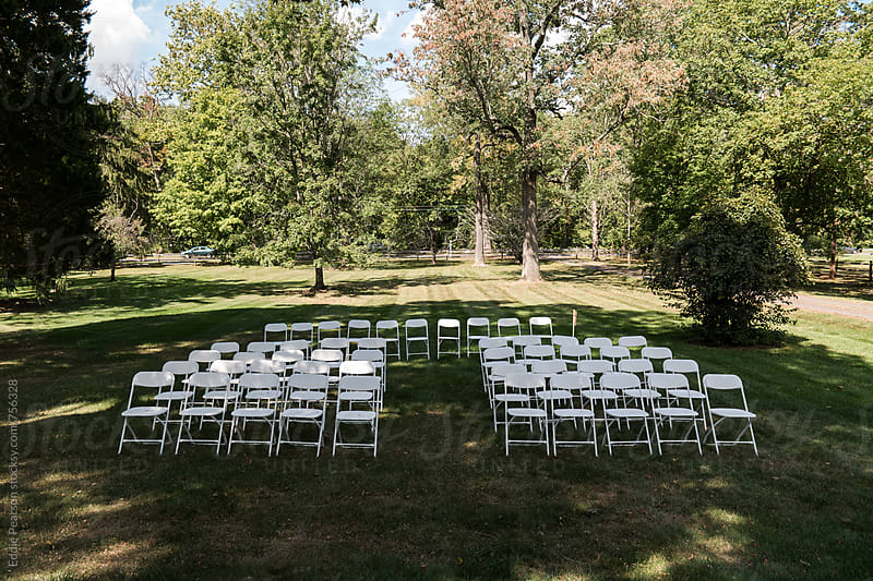 Empty white chairs at a wedding by Eddie Pearson for Stocksy United