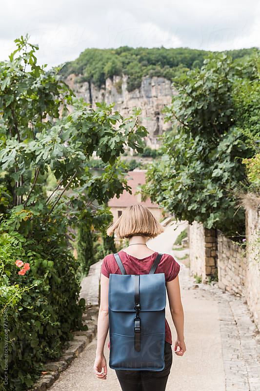 Young woman walking down a path in a village by Lior + Lone for Stocksy United