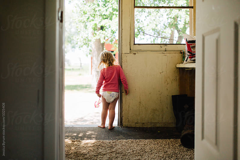 Toddler girl in red sunglasses standing on the porch. by Jessica Byrum for Stocksy United