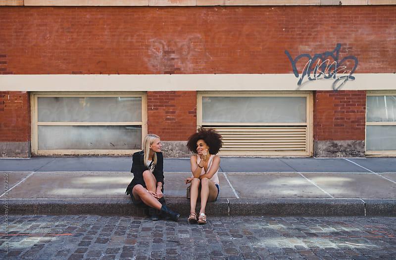 Friends talking on cobblestone street in Soho by Lauren Naefe for Stocksy United