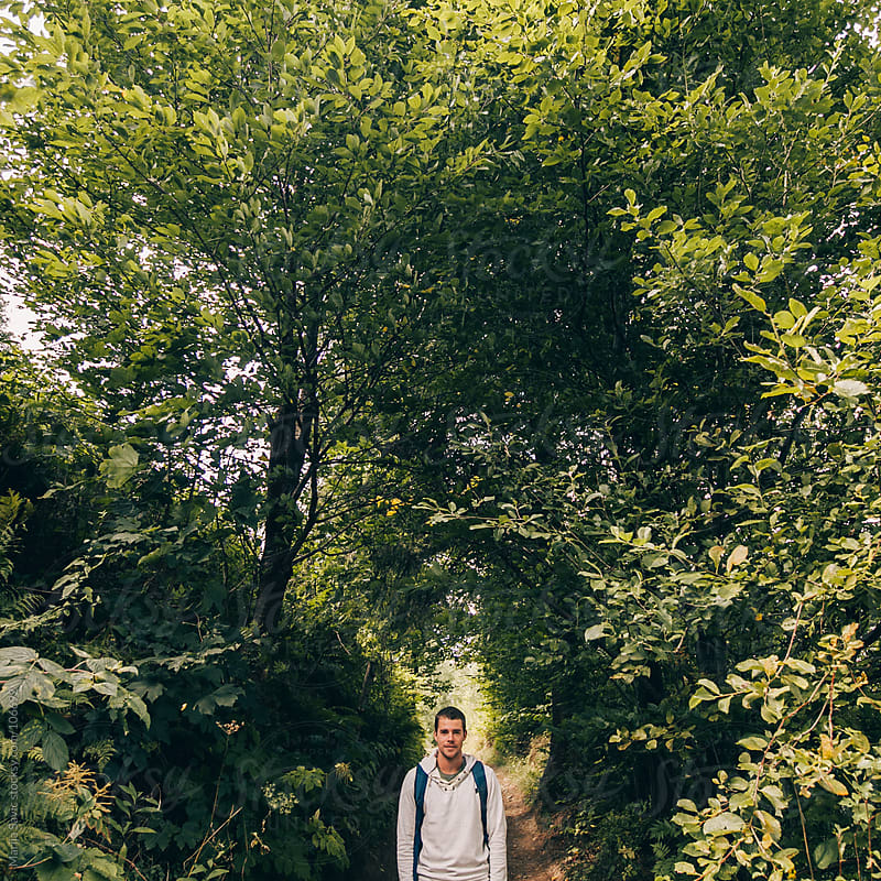 Man surrounded  by trees. by Marija Savic for Stocksy United