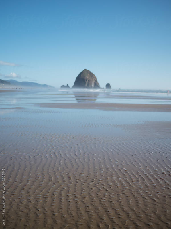 Ripples in sand in front of ocean and giant rock. Cannon Beach, Oregon by Jeremy Pawlowski for Stocksy United