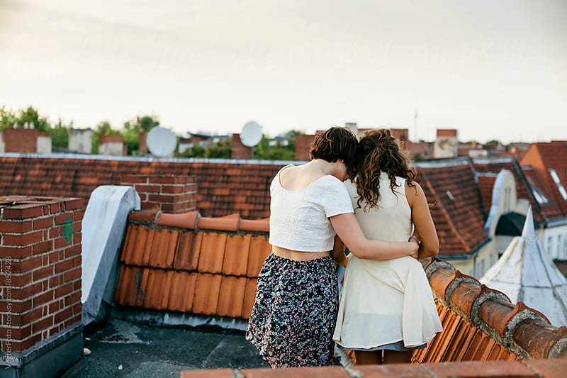 Young female couple standing on a rooftop by VegterFoto for Stocksy United