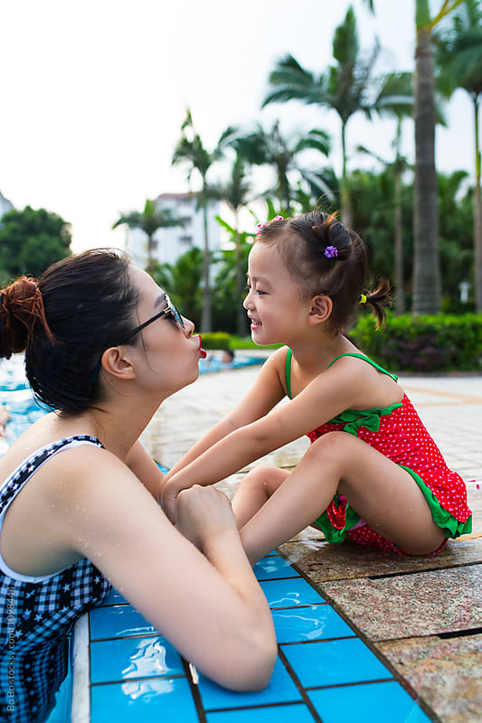 woman and her daughter in the swimming pool by Bo Bo for Stocksy United