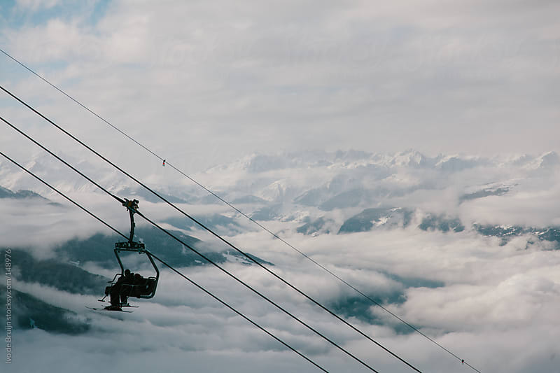 Chairlift with skiers  in the french mountains or Alps by Ivo de Bruijn for Stocksy United