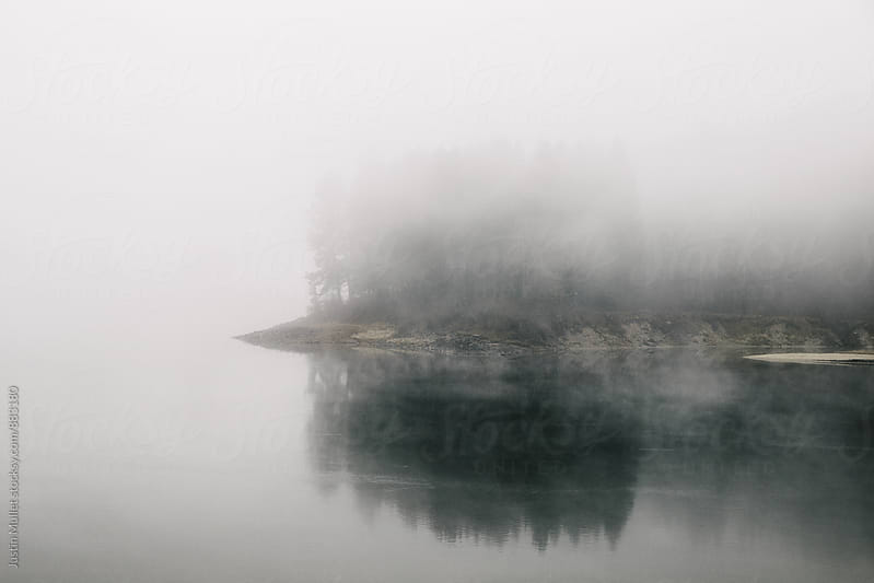 An island on a river nearly hidden by thick fog by Justin Mullet for Stocksy United