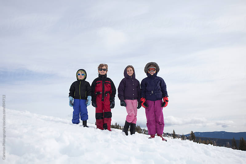 Four kids on top of a snowy ridge by Carleton Photography for Stocksy United
