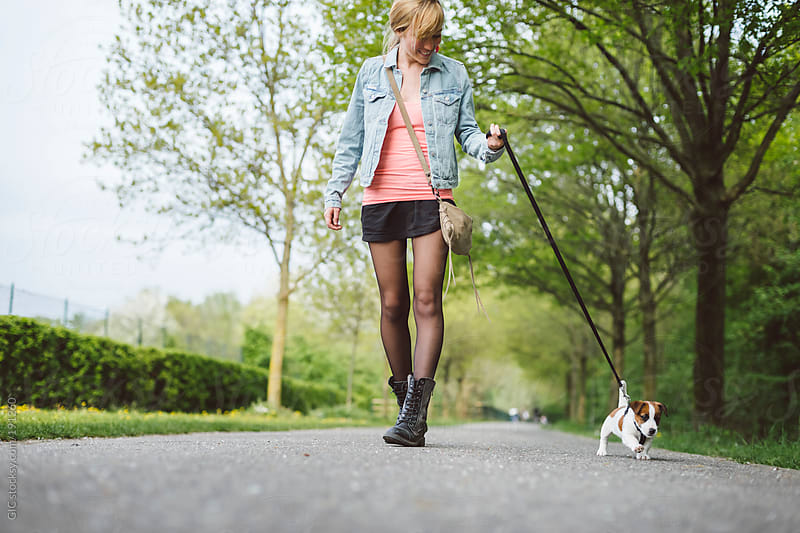 Young woman holding dog leash during a promenade in the park by GIC for Stocksy United