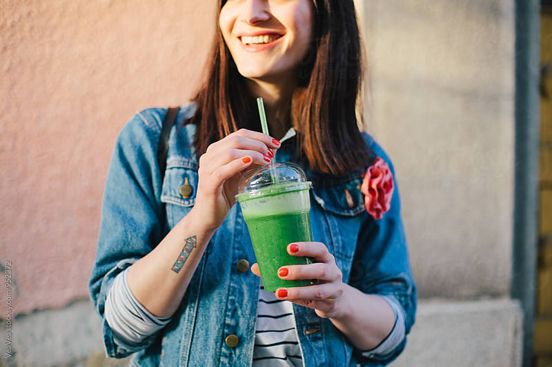 Woman drinking smoothie in the street by VeaVea for Stocksy United