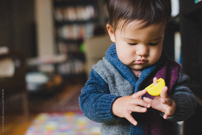 Toddler playing with wooden toy by Lauren Naefe for Stocksy United