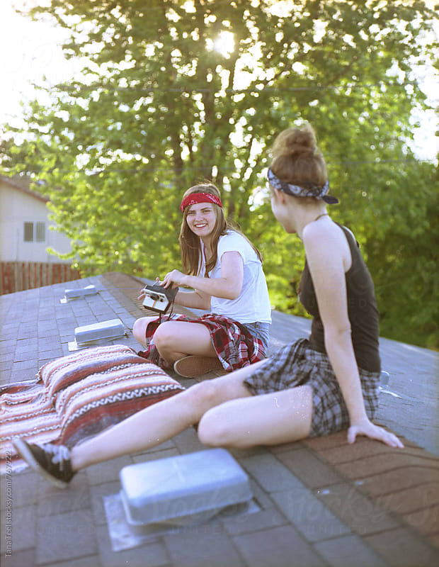 teenagers sitting on rooftop with polaroid camera by Tana Teel for Stocksy United