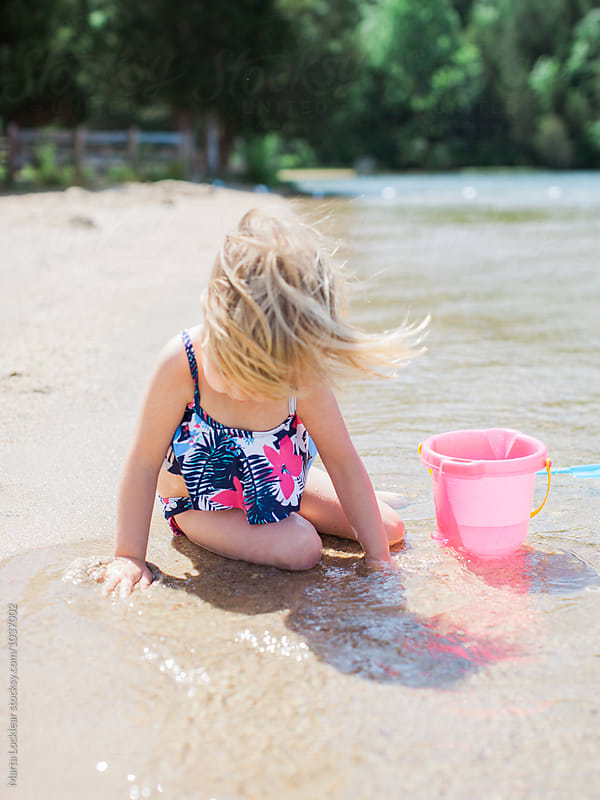 Little girl playing with a bucket at the beach by Marta Locklear for Stocksy United