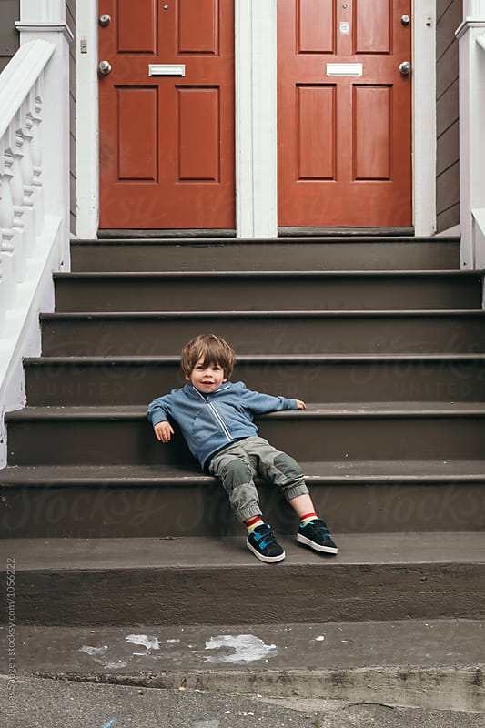 Toddler sitting and relaxing like he owns the place. by Lucas Saugen for Stocksy United
