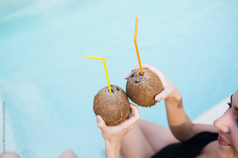 Female friends drinking coconut by the pool by Jovana Rikalo for Stocksy United