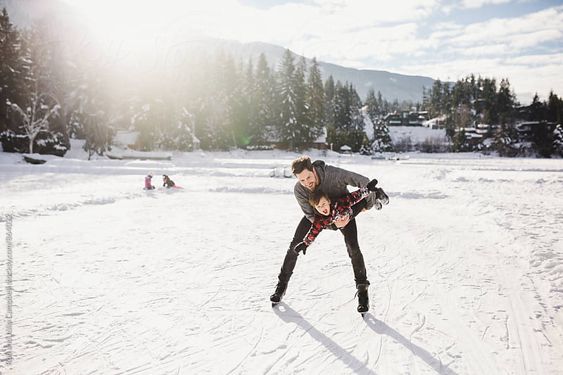 Active young dad playing with son on frozen lake in winter by Rob and Julia Campbell for Stocksy United