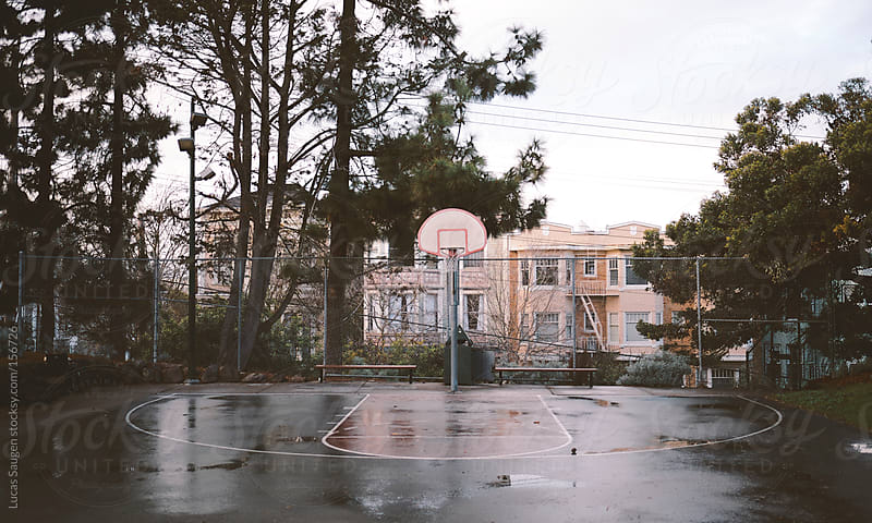 Wet rainy day on a small half basketball court. by Lucas Saugen for Stocksy United