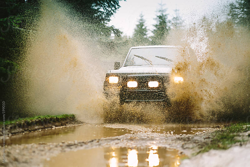 4WD vehicle going through water by Marko Milovanović for Stocksy United