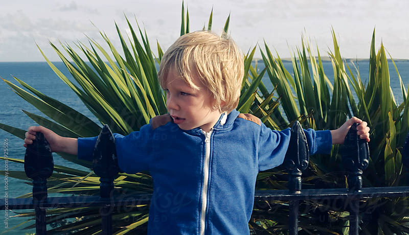 Child leaning on the fence by the beach by sally anscombe for Stocksy United