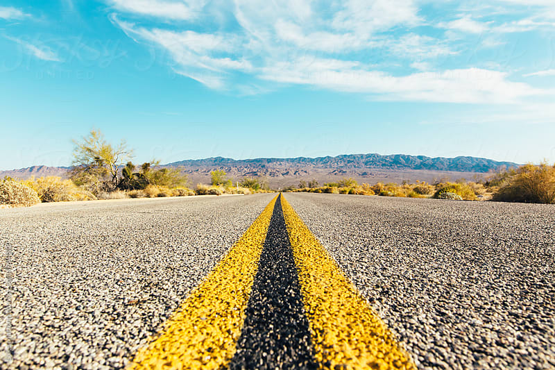 Middle Painted Yellow Lines Of Desert Highway by Luke Mattson for Stocksy United